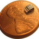 A penny laying flat with a tiny device on it