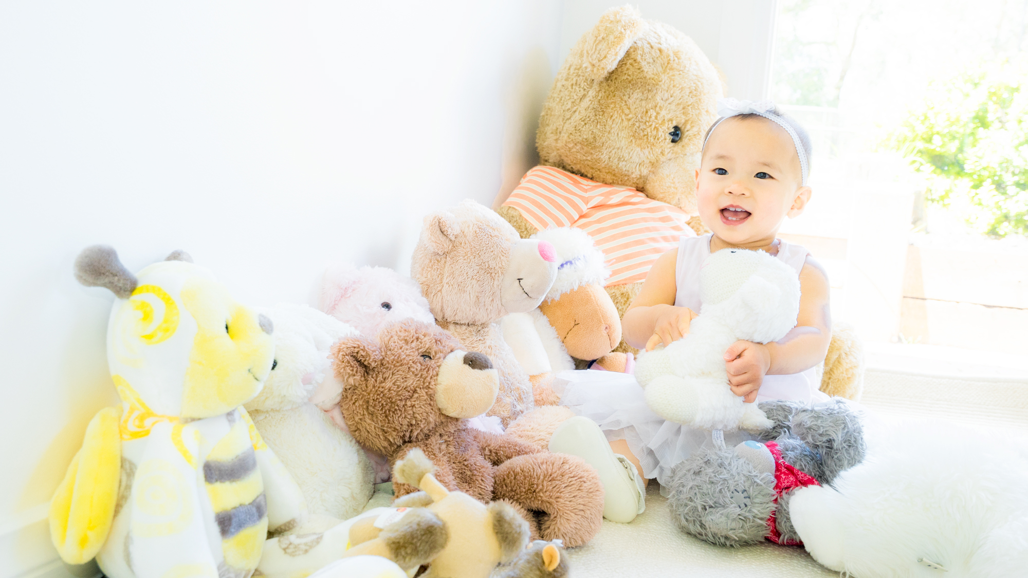 Asian baby portrait with plush toys by Black Avenue Productions