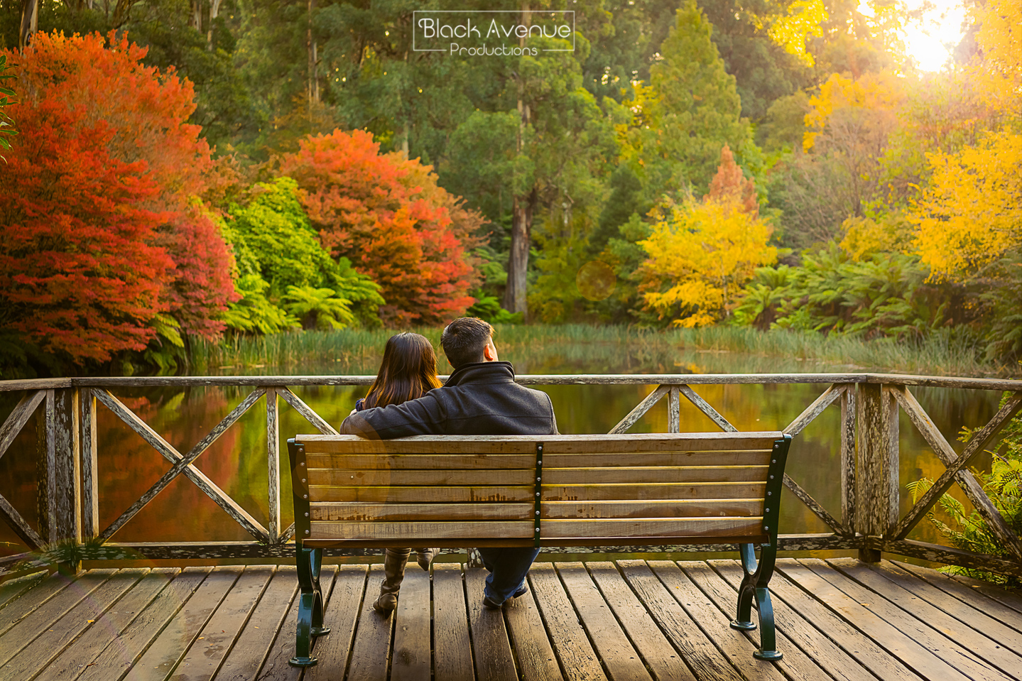 boy and girl taking romantic candid photo by the Yarra River looking at yellow orange red autumn tree leave in Melbourne wedding