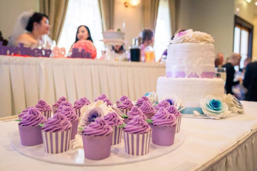 purple cupcake wedding cake at reception table with bridal party at the background at Merrimu Receptions by Black Avenue Productions