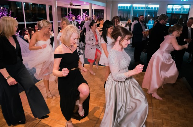candid moment of bridal party all dancing in wedding reception having fun