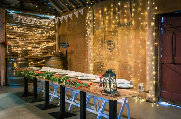 beautiful rustic bridal table setting at Baxter Barn Wedding Reception with fairy lights on the wall