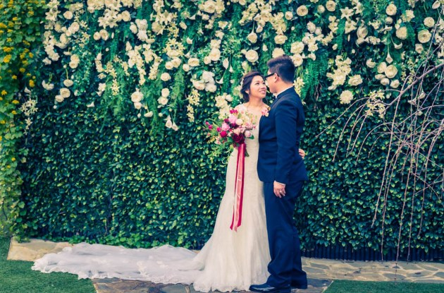 bride groom photo showing couple holding flower bouquet standing in front of greenery vertical wall in love at Bram Leigh Receptions