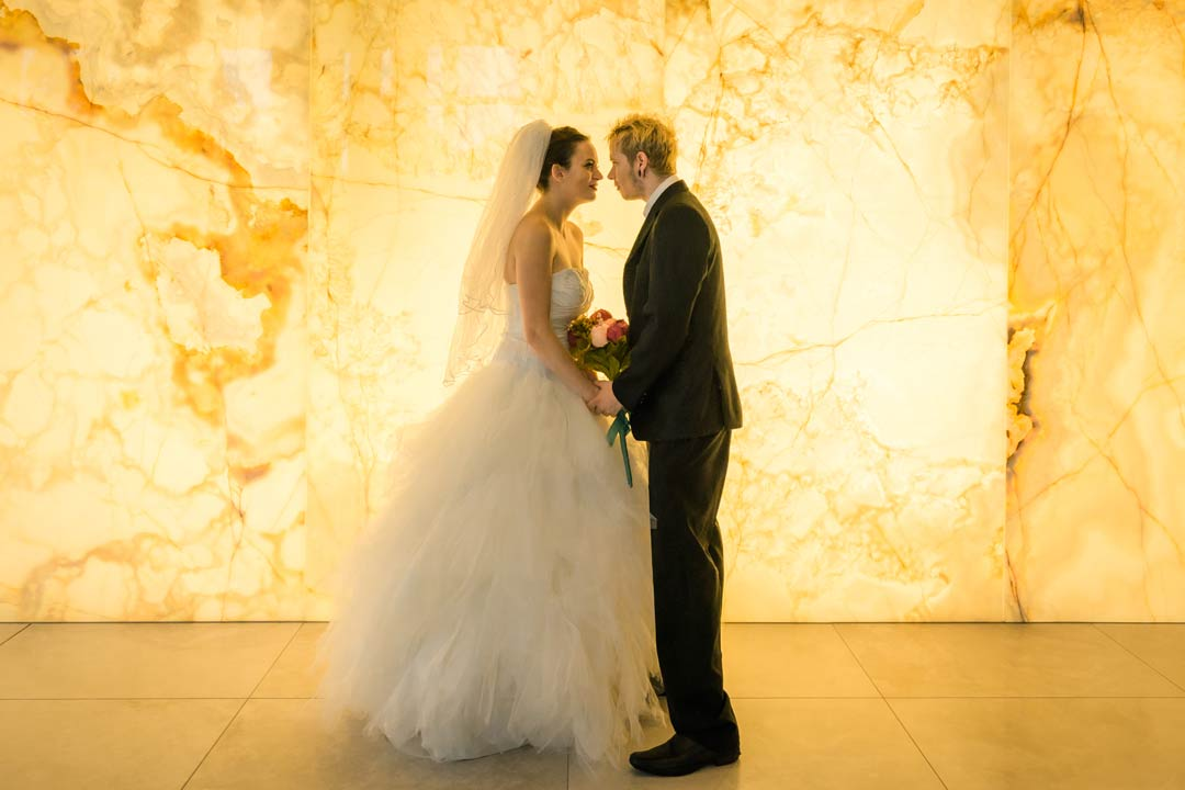 fun wedding photo of bride and groom staring at each other on yellow LED light wall in Docklands Melbourne reception