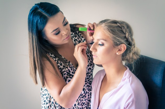 candid moment of makeup artist put mascara on bride capture by Melbourne wedding photographers