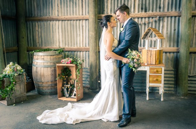 candid moment of married couple in wedding dress holding hands in rustic barn setting in inglewood estate Melbourne