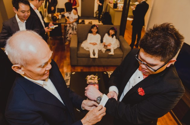 father helping son to put on his watch to get ready for wedding day in Richmond Melbourne Victoria Australia home