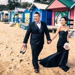 natural moment of bride and groom in black bridal dress walking along the beach in Australia Brighton beach house