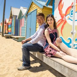 Summer time engagement photo of young engaged couple sitting by a colourful beach house in Brighton Melbourne