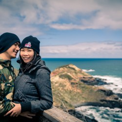 sweet couple hug each other on mountain top smiling for Melbourne wedding photographer Black Avenue Productions with ocean and wave background in 2017