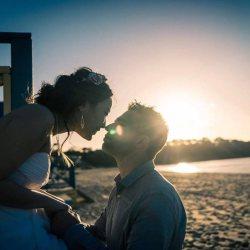 engaged couple kissing happily at beautiful sunset by the Mornington Peninsula beach