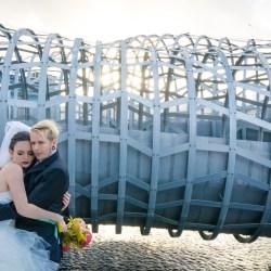 bride and groom hugging in Dockland outside a futuristic metal steel bridge