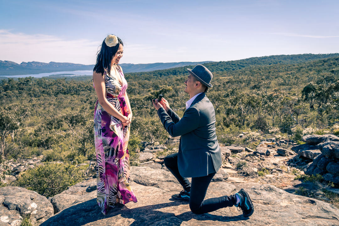 boyfriend surprise his girlfriend with an engagement ring on hand and propose by the balconies at Reeds look out in Australia hill cliff