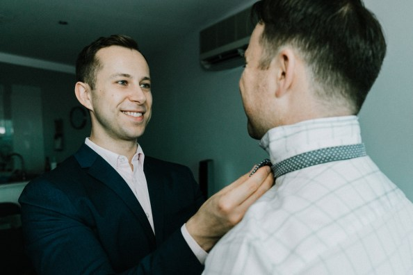 happy gay man help his fiancé to wear a tie for a Melbourne gay wedding party