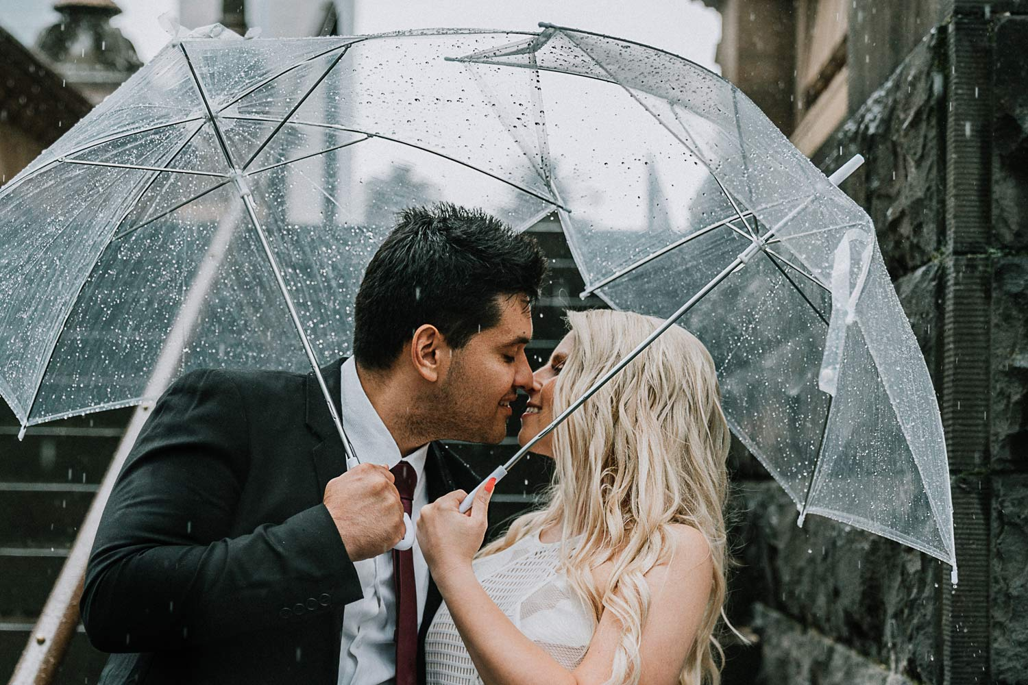 Melbourne couple holding clear umbrellas during a rainy day for pre wedding photo shoot