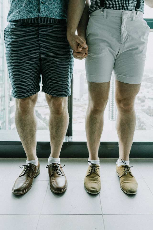 gay marriage photo showing two grooms standing side by side showing their wedding shoes on their Melbourne gay wedding day