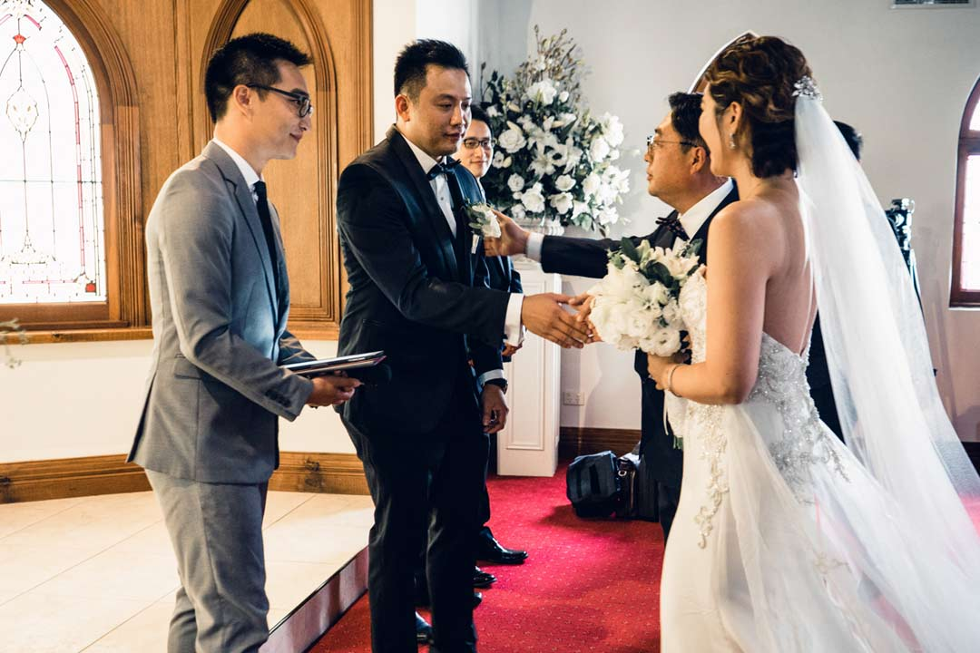 the moment that father hand bride to groom in church wedding capture by Black Avenue Productions