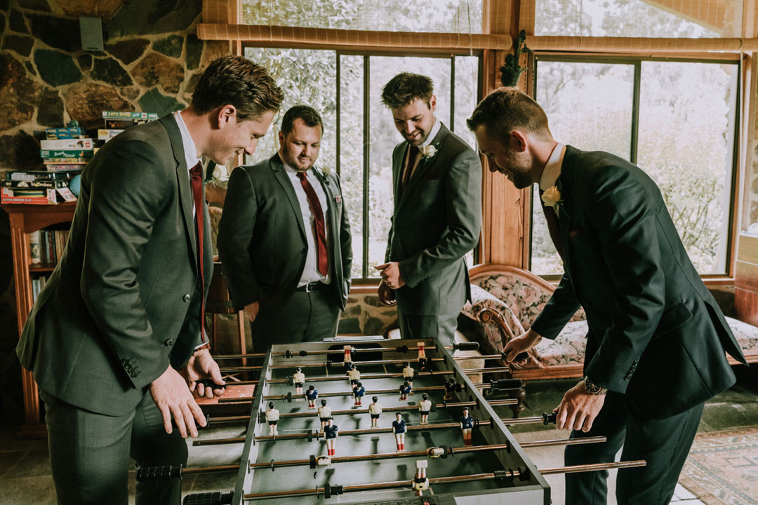 happy groom and groomsmen play football in their rustic farmhouse