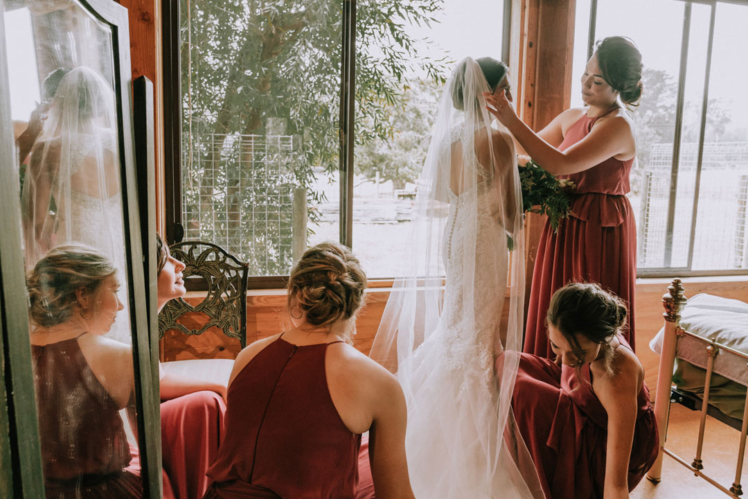 bride getting ready with bridesmaids help