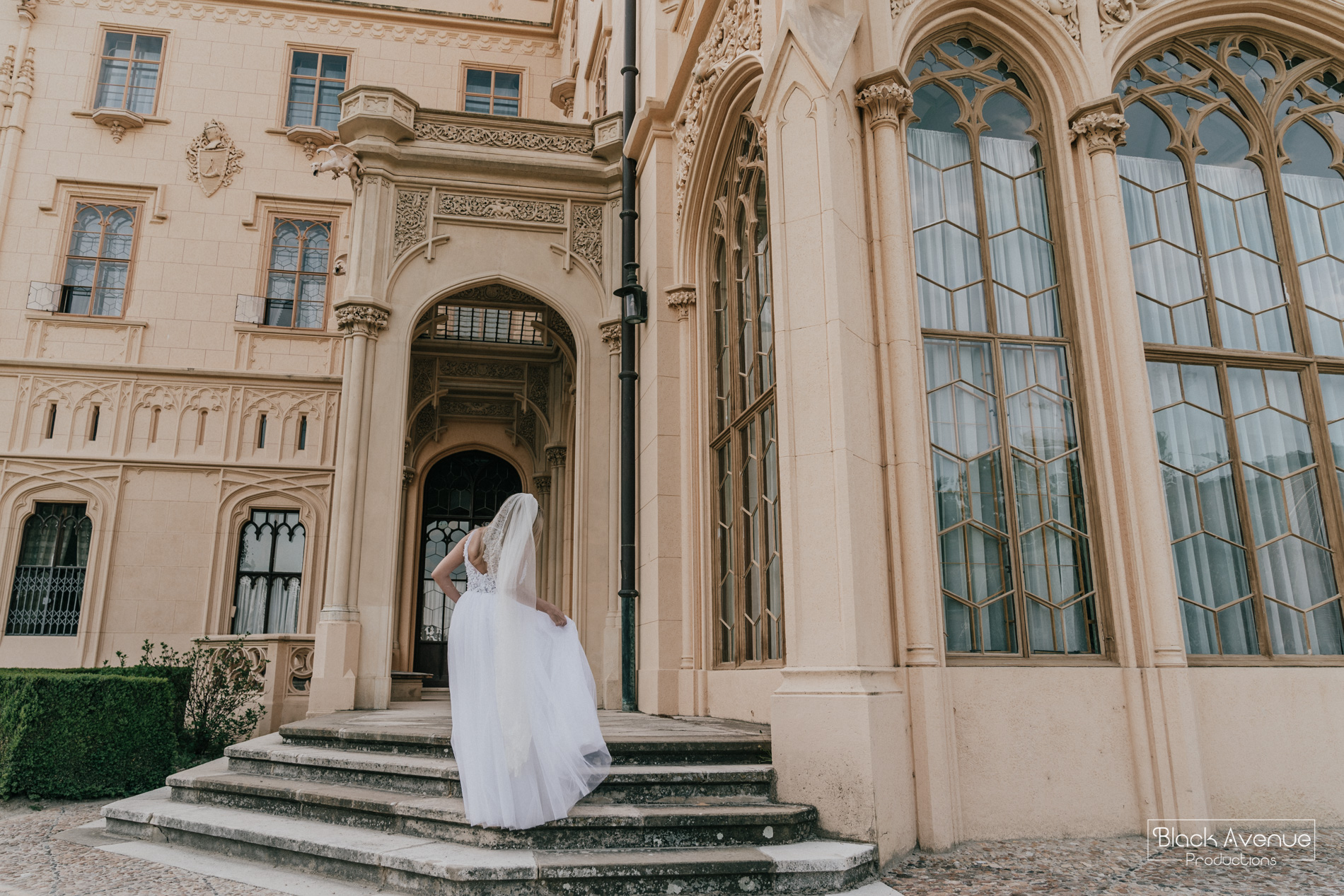 image of the back of a stunning bride in Leah S Design bridal dress running to a castle captured by destination wedding photographer Derek Chan and Lowina Blackman