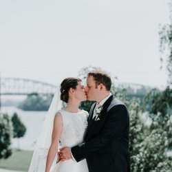 Destination Wedding in Esztergom Bazilica with Melbourne married couple kissing in front of a bridge captured by wedding photographers Derek Chan from Black Avenue Productions in Europe