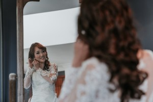 bride looking at mirror put earrings on in her Leah S Design wedding gown at Marybrooke Manor