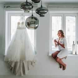 beautiful blonde bride sitting on balcony in Vienna home for bride getting ready photo on your wedding day