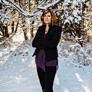 Tracey S. Phillips in dark clothing standing in a snowy landscape