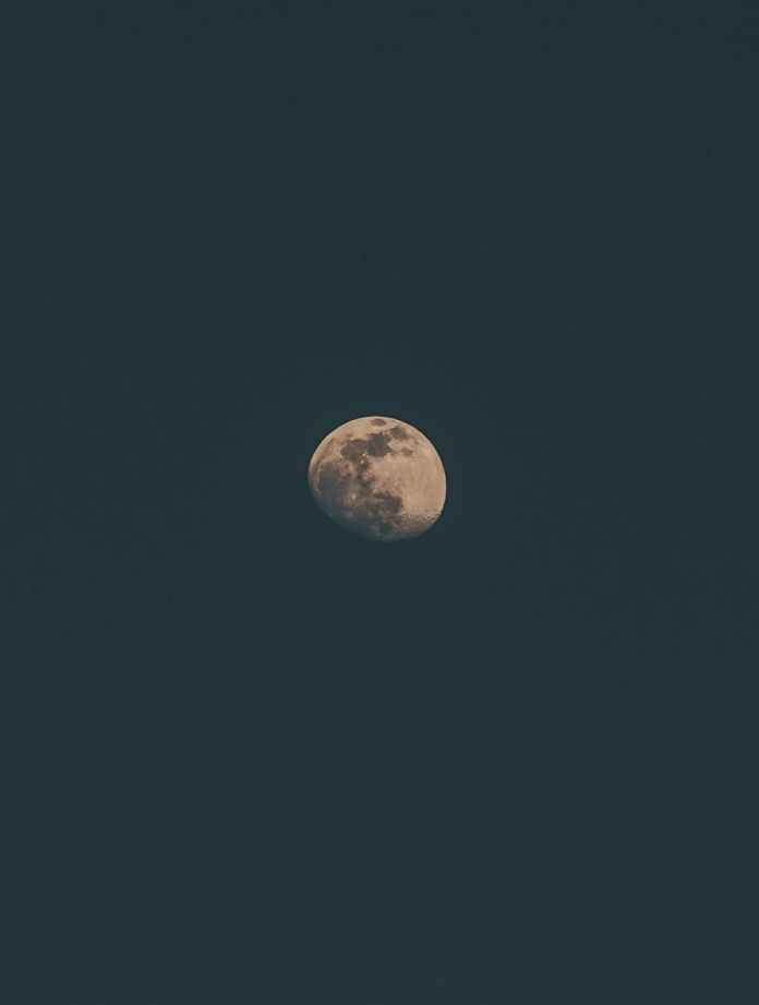 luminous moon shining on dark sky