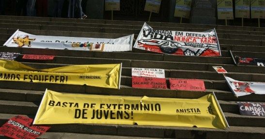 Signs remember the massacre and call for an end to the extermination of young people