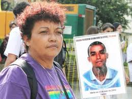 Débora Maria da Silva displays a photo of her son Edson Rogério Silva dos Santos who was killed by a death squad in 2006