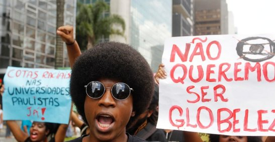 "Sign at left: ""Racial quotas in the São Paulo Universities NOW!"" Sign at right: ""We don't want to be Globeleza"""