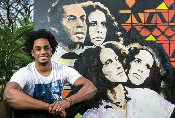 Artist Muha Bazila next to a portrait of the 'Doces Bárbaros', a 1976 album by the group of the same name. The featured top Brazilian Popular Music artists Gilberto Gil, Caetano Veloso, Maria Bethânia and Gal Costa