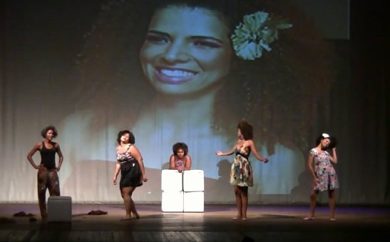 Still from 'Pentes'. In the background appears an image of singer Vanessa da Mata. The scene presents numerous other black women such as singer Beyoncé, actress Lucy Ramos and others who are presented as references for the plays characters.