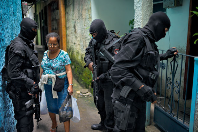 finishing-her-errands-a-favela-resident-passes-military-police-taking-part-in-a-training-exercise-david-alan-harvey