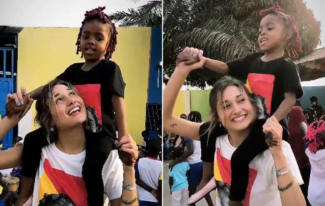 Sasha brinca e dança com crianças, em Angola