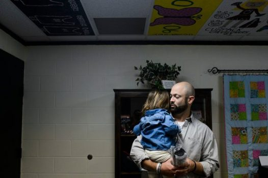 Bo Copley held his youngest daughter, Merritt, 2, while waiting for the Thanksgiving assembly at Ambassador Christian Academy in Williamson, W.Va. (Christian Tyler Randolph for The New York Times)