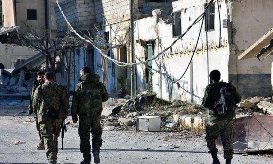 Syrian soldiers in Aleppo's eastern Masaken Hanano district. (Photograph: Sana/EPA)