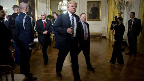 President Donald Trump walks with Vice President Mike Pence, left, and Sean Spicer, White House press secretary, right, in the East Room of the White House in Washington on Jan. 22, 2017. (Photographer: Andrew Harrer/Bloomberg)
