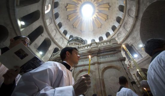 Christian pilgrims light candles during the Easter Sunday procession at the Church of the Holy Sepulchre, traditionally believed by many Christians to be the site of the crucifixion and burial of Jesus Christ, in Jerusalem, Sunday, April 16, 2017.