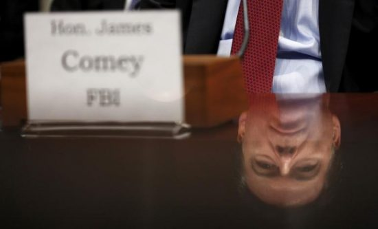 """FILE PHOTO: FBI Director James Comey is seen in a reflection as he testifies in a House Appropriations hearing on """"World Wide Threats"""" on Capitol Hill in Washington February 25, 2016. REUTERS/Kevin Lamarque/File Photo"""