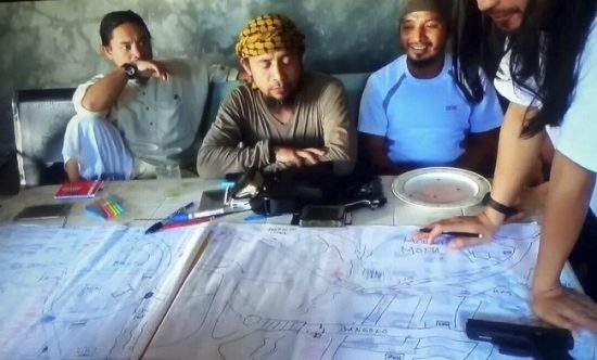 This image taken from undated video shows the purported leader of the Islamic State group Southeast Asia branch, Isnilon Hapilon, center, at a meeting of militants at an undisclosed location. The images offer a rare glimpse into the clandestine operations of insurgents who followed through two weeks ago with an unprecedented assault on the lakeside city of Marawi, parts of which they still occupy today.