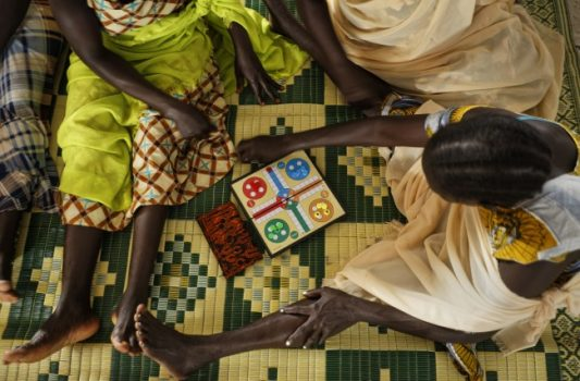 In this photo taken Saturday, June 3, 2017, South Sudanese refugee women who suffered sexual or other gender-based violence play a board game at a women's center focusing on such violence, run by the aid group International Rescue Committee, in Bidi Bidi, Uganda. Gathered under tarpaulins baking in the sun, some of hundreds of survivors of sexual violence meet regularly at such centers to help each other get beyond their trauma. (Ben Curtis/Associated Press)