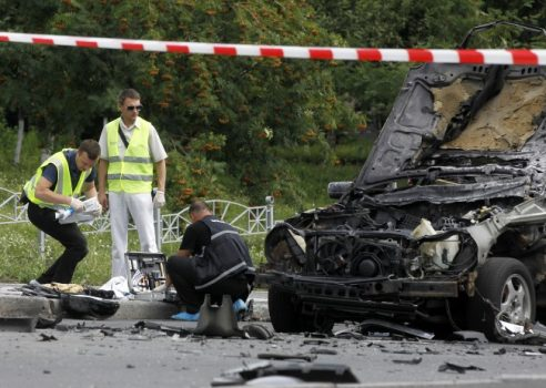 Forensic experts examine the wreckage of a car in Kiev, Ukraine, Tuesday, June 27, 2017. Ukrainian authorities say that a senior military intelligence officer has been killed in a car bomb in the country's capital. Police say that the driver of a luxury car has been killed instantly as the vehicle blew up at a Kiev intersection. (Sergei Chuzavkov/Associated Press)