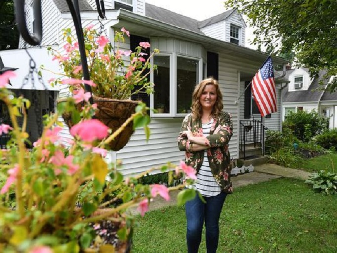 No place like home: Meagan Walsh, 25, stands in front of her house in Allentown, PA, that she bought with cash she saved after returning home to her parents' house after college. (Photo by Robert Deutsch, USA TODAY)