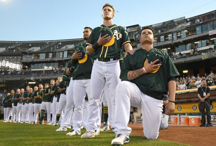 Bruce Maxwell of the Athletics kneels in protest next to teammate Mark Canha. (Thearon W. Henderson/Getty Images)