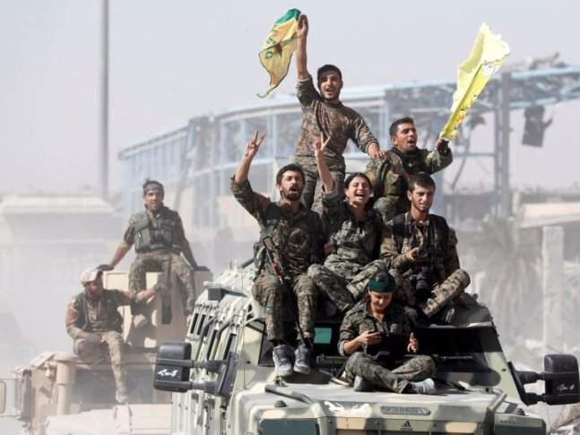 Syrian Democratic Forces fighters ride military vehicles as they celebrate victory in Raqqa. (Thomson Reuters)