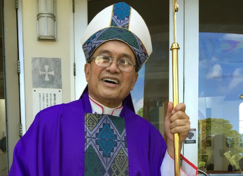 This November 2014 file photo shows Archbishop Anthony Apuron standing in front of the Dulce Nombre de Maria Cathedral Basilica in Hagatna, Guam. (AP Photo/Grace Garces Bordallo, File)