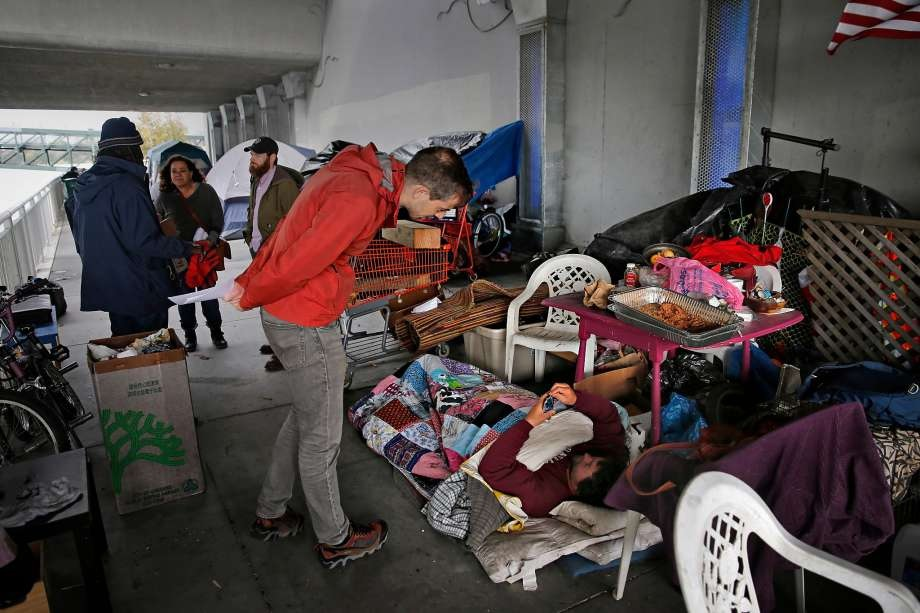 Dr. Colin Buzza visits an Oakland homeless camp as part of a street treatment program for opioid addiction and mental illness. (Photo: Michael Macor, The Chronicle)