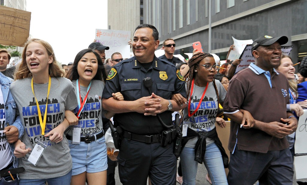 "Police Chief Art Acevedo of Houston, center, walking with demonstrators during a ""March for Our Lives"" protest in March. After a school shooting in Santa Fe, Tex., on Friday, he wrote on Facebook that he had hit ""rock bottom"" about inaction on gun control. (Credit: David J. Phillip/Associated Press)"